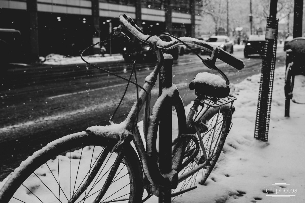 black and white photo of a lonely bicycle on a snowy day.