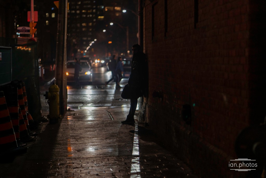 Dark rainy shot of a young man brooding against a brick wall lit by traffic headlights.