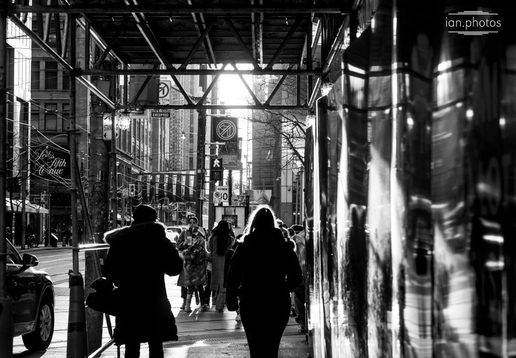 black and white photo of people on a crowded city sidewalk.