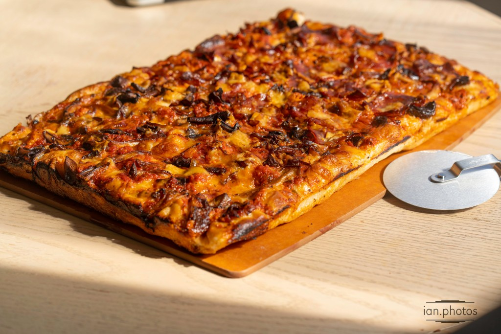 Large pizza on a wooden table and cutting board.