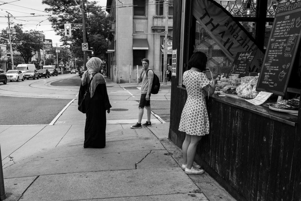 Black and white photo of a street corner. A woman in a headscarf watches another woman in a dress as a man with a cigarette glares at the camera.